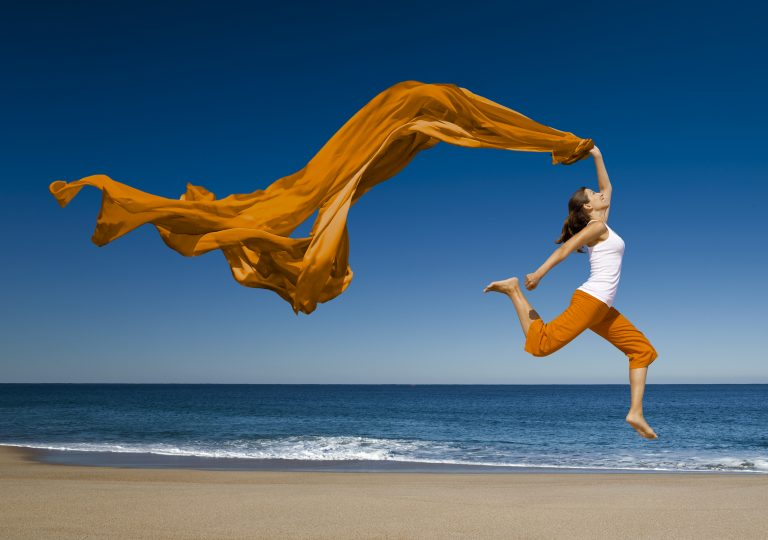 Woman with orange scarf jumping in the beach